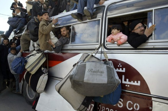 Palestinian families crammed into a vehicle as they pass through the Rafah border crossing