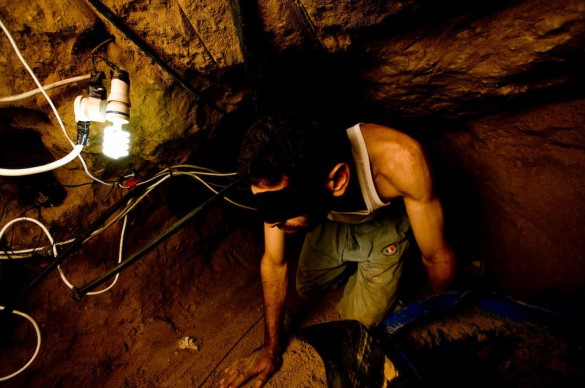 A Palestinian tunnel worker crawls beneath the Gaza/Egypt Egypt border