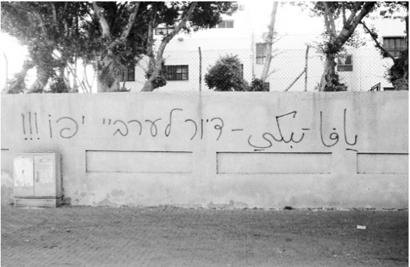 "Graffiti in the gentrified `Ajami neighborhood: ""Jaffa Weeps"" (Arabic) - ""Housing for the Jaffa Arabs!!! (Hebrew)."""