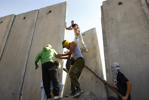 Activists dismantle a section of the Wall at Qalandiya