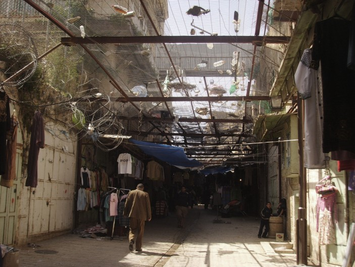 A city divided in section: a high level cage and tarpaulins protect the street from the settlers who regularly drop rubbish, rocks, etc. from above. It is not enough though against filthy water and urine (John Lewicki)